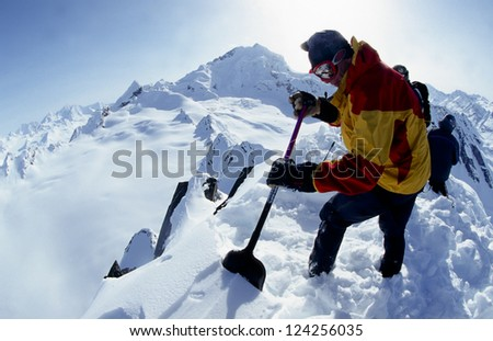 VALDEZ, ALASKA - APRIL 24: Unidentified mountain guide preparing a helicopter landingzone on a mountain peak in the Chugach Mountains on April, 24, 2002. Valdez is the hub for Heli-skiing in Alaska. - stock photo