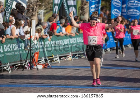 VALENCIA - APRIL 6: unidentified runner finishes race in women race against cancer in Valencia on April 6, 2014 in Valencia, Spain