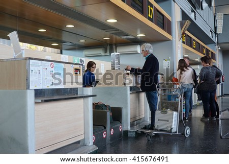 VALENCIA, SPAIN - APRIL 30, 2016: Airline passengers checking in at an airline counter in the Valencia Airport. About 4.98 million passengers passed through the airport in 2015. - stock photo