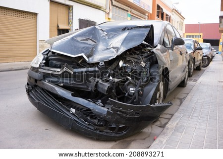 VALENCIA, SPAIN - AUGUST 4, 2014: A crash car parked on the street in Valencia waiting for repair. A 1985 study by K. Rumar, found that 57% of car crashes were due solely to driver error. - stock photo