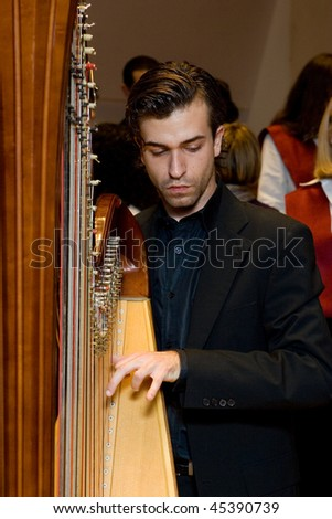 VALENCIA, SPAIN - DECEMBER 4: A musician plays the harp as the choir of the University Catolica de Valencia performs at the Palau de la Musica concert hall on December 4, 2009 in Valencia, Spain. - stock photo