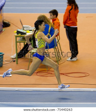 """VALENCIA, SPAIN - FEBRUARY 20: Competitor of 1500m women """"Macias Chow Isabel"""" at first place of the Spanish indoor national championships at Valencia on February 20, 2011 in Valencia, Spain - stock photo"""
