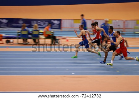 VALENCIA, SPAIN - FEBRUARY 19: Race of the Indoor track and field spanish national championship. Runners in the middle of men's 60m sprint on February 19, 2011 in Valencia, Spain - stock photo