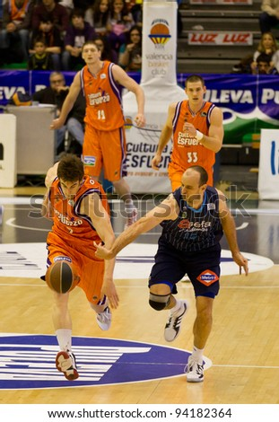 VALENCIA, SPAIN - JANUARY 28: Carlos Jimenez (blue) and Victor Claver (orange) in action during the league match between Valencia Basket and Estudiantes, 85-71, on January 28, 2012, in Valencia, Spain - stock photo