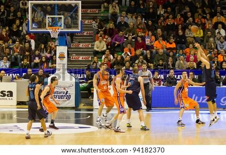 VALENCIA, SPAIN - JANUARY 28: Carlos Jimenez (blue shirt #10)  three-point shot during the league match between Valencia Basket  and Asefa Estudiantes, 85-71, on January 28, 2012, in Valencia, Spain - stock photo