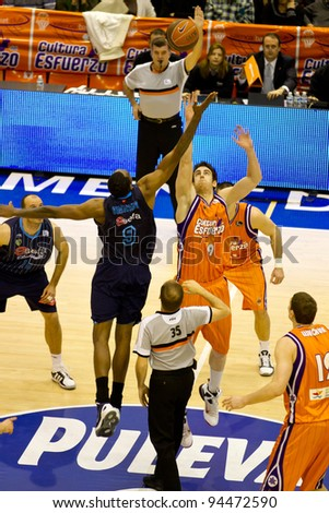 VALENCIA, SPAIN - JANUARY 28: Cedric Simmons (Blue) and Victor Claver (orange) starting the match between Valencia Basket and Asefa Estudiantes, 85-71, on January 28, 2012, in Valencia, Spain - stock photo