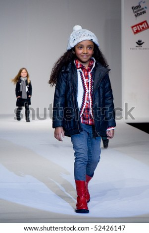 VALENCIA, SPAIN - JANUARY 23: Model Alicia Sanz, age 12, of Valencia on the catwalk for the Valencia Fashion Show with the designer Tumble'n Dry on January 23, 2010 in Valencia, Spain. - stock photo