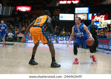 VALENCIA, SPAIN - JANUARY 21: Runkauskas with ball and Sato during Eurocup match between Valencia Basket Club and CSU Asesoft at Fonteta Stadium on January 21, 2015 in Valencia, Spain