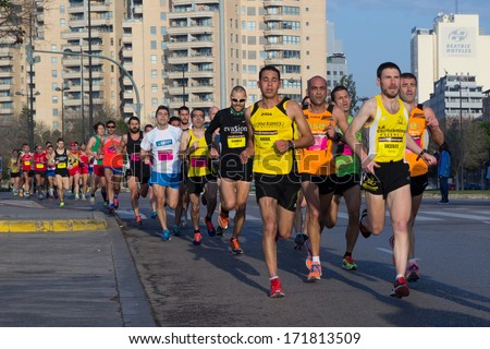 VALENCIA, SPAIN - JANUARY 12, 2014: Runners compete in the 10K Divina Pastora Valencia run. Over 10,500 people participated in the run.  - stock photo