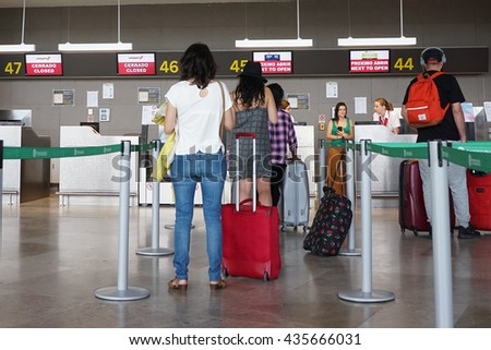 VALENCIA, SPAIN - JUNE 10, 2016: Airline passengers checking in at an airline counter in the Valencia Airport. About 4.98 million passengers passed through the airport in 2015. - stock photo