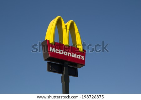 VALENCIA, SPAIN - JUNE 13, 2014: McDonalds logo sign with blue sky in Valencia. It is the world's largest fast food chain, over 31,000 restaurants worldwide, serve 58 million customers each day. - stock photo