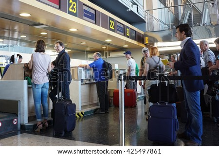 VALENCIA, SPAIN - MAY 21, 2016: Airline passengers checking in at an airline counter in the Valencia Airport. About 4.98 million passengers passed through the airport in 2015. - stock photo