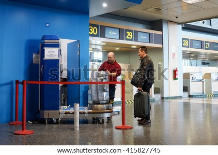 VALENCIA, SPAIN - MAY 5, 2016: An airline passenger having his luggage wrapped in industrial strength cling film. Wrapping your luggage in cling film can provide peace of mind ahead of your journey. - stock photo