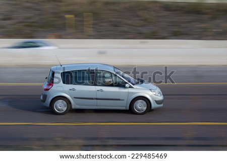 VALENCIA, SPAIN - NOVEMBER 7, 2014: A blue Renault Scenic auto on the highway in Valencia. The Scenic is a compact mult-purpose vehicle (MPV) produced by French automaker Renault. - stock photo