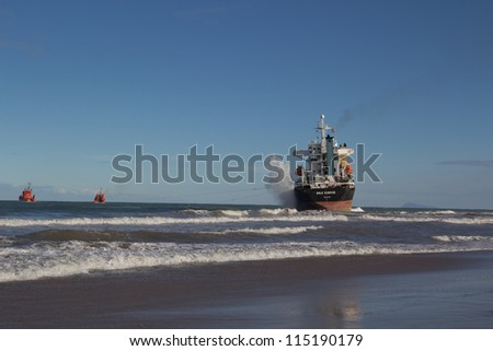 VALENCIA, SPAIN - SEPT 30: Two tug boats trying to save the cargo ship BSLE Sunrise of Panama after it  runs aground at the El Saler Beach during a big storm on September 30, 2012 in Valencia, Spain.