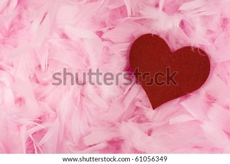 Valentin Love Theme   Red Fabric Heart Lying In Pink Feathers Background.