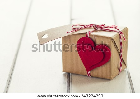 Valentine. A paper parcel wrapped tied with a tag. A red heart on a gift box wrapped with paper kraft and tied with red & white baker's twine on a white wooden table. Vintage Style. - stock photo
