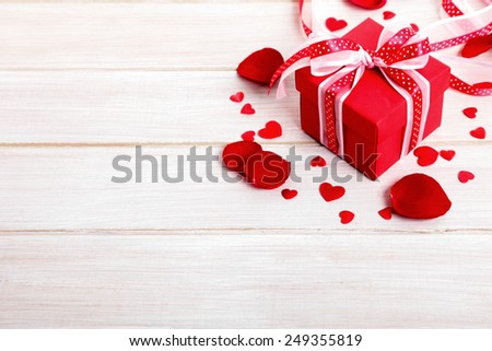 Valentine background of gift box and rose petals on white wood. Space for copy. - stock photo