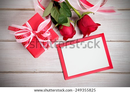 Valentine background of gift box, two red roses and blank card with envelope on wood. Space for copy.