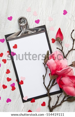 Valentine background with coloured hearts and flowers on white wooden background