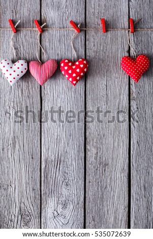 Valentine background with diy sewed pillow hearts row border on red clothespins at rustic gray wood planks. Happy lovers day card mockup, copy space, vertical composition