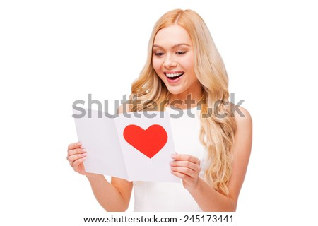 Valentine card from him. Beautiful young blond hair woman holding valentine card and smiling while standing isolated on white - stock photo