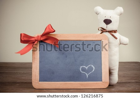 Valentine card with Teddy bear, heart on wooden black board with bow in vintage style - stock photo
