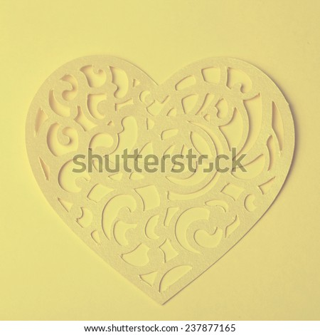 Valentine carving heart cutted from paper on the paper background, vintage toned image, instagram effect - stock photo