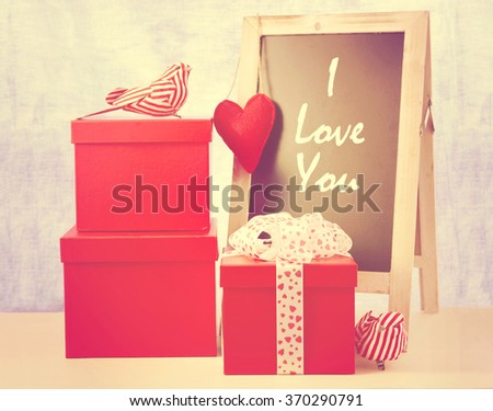Valentine chalkboard with a stack of red gifts and bird ornaments on white wood table and I Love You message, with applied retro vintage style filters.  - stock photo