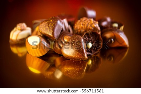 Valentine Chocolates. Assorted Chocolate Candies. Chocolate Sweets. Candy Border Design over Golden Background. Heart Shaped Chocolate.