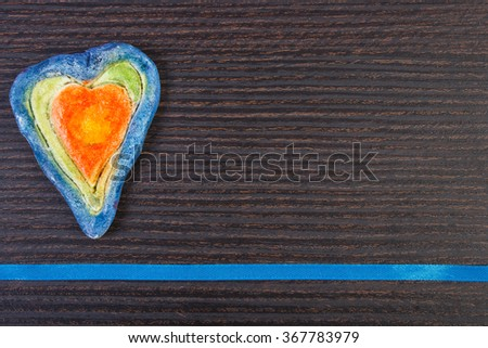 Valentine colorful heart made of salt dough and ribbon on wooden background, decoration for Valentines Day, symbol of love, copy space for text - stock photo