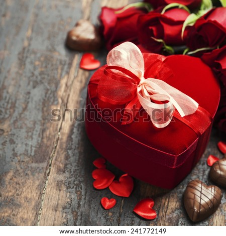Valentine composition with roses and gift box on wooden background - stock photo