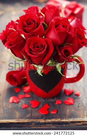 Valentine composition with roses and hearts on wooden background - stock photo