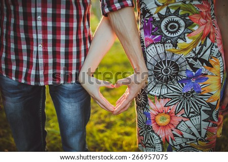 Valentine Couple in love showing Heart with their fingers. - stock photo