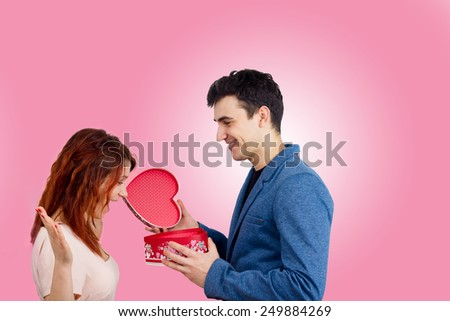 Valentine Couple. Portrait of Surprised red head Girl and her Handsome Boyfriend holding a gift heart . Love Concept. Laughing Happy Lovers. Valentines Day - stock photo