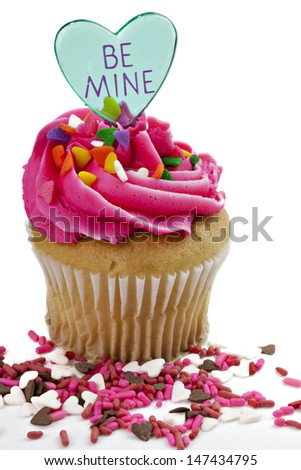 Valentine cupcake with pink frosting and heart with BE MINE on it - stock photo
