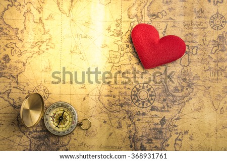 Valentine day background.Old compass on vintage map with red heart. Retro filter. Direction to real love of your heart concept. - stock photo