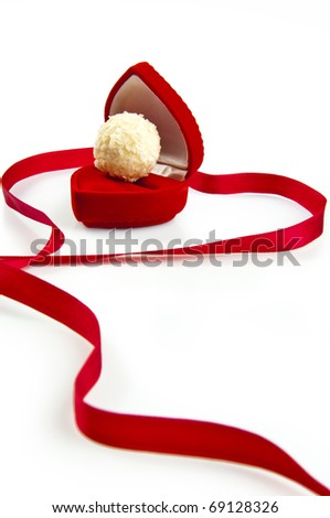 Valentine day concept: candy in red gift-box and shiny red satin ribbon. Macro shot, isolated on white background - stock photo