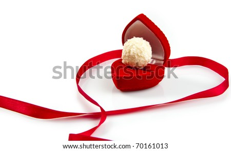 Valentine day concept: candy in red heart-shape gift-box and red satin ribbon. Macro shot, isolated on white background - stock photo