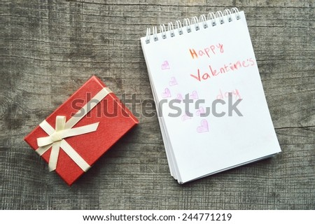 valentine day concept.notebook with the words Happy Valentine's Day.hearts. on a wooden background - stock photo