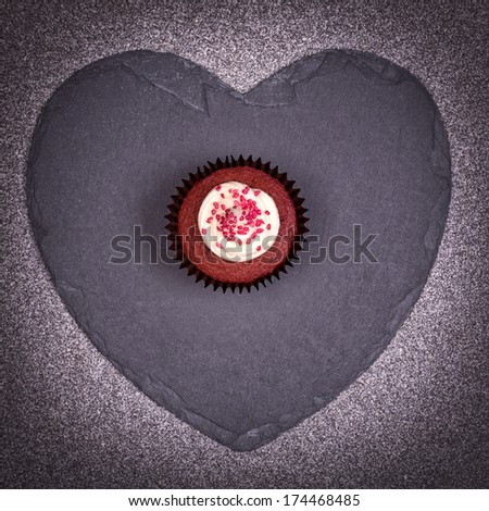 Valentine day gift of a red velvet cupcake over a slate heart. - stock photo