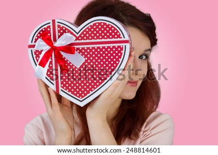 Valentine Day-Girl smiling and hiding behind a Valentine heart gift.