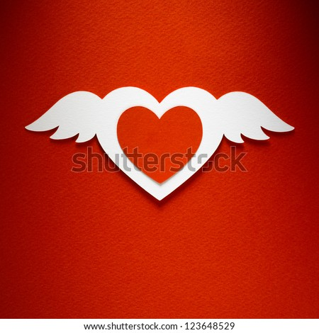 Valentine day heart with angel wings made of paper on red paper background - stock photo