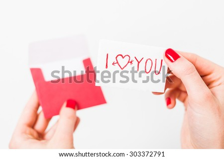 Valentine day I love you gift card in red envelope in women hands on white background - stock photo