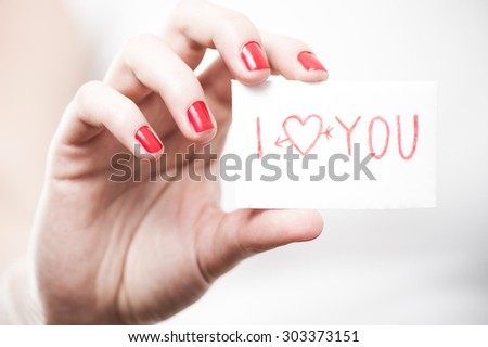 Valentine day I love you gift card in women hands on white background - stock photo
