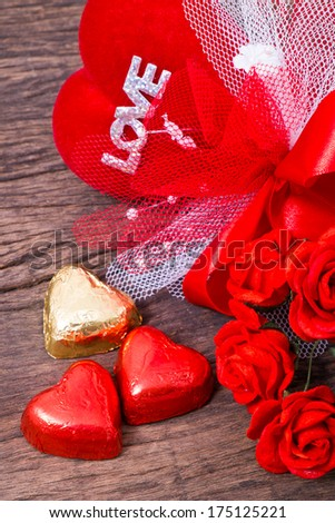 Valentine decoration, heart shaped chocolate, roses, ribbon, heart and love word on wooden table top