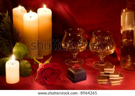 Valentine dinner with rose, candles, gift box, candies and two glasses of white wine on carmine velvet background. - stock photo