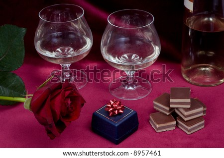 Valentine dinner with rose, gift box, candies and two glasses of white wine on purple velvet background. - stock photo