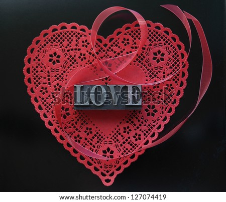 Valentine doily with the word love in metal type and a red ribbon - stock photo