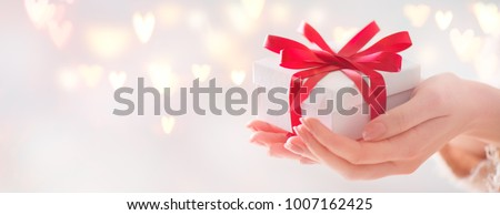 Valentine gift. Beauty Woman hands holding Gift box with red bow over holiday  background with glowing hearts bokeh, close-up. pastel colors. Wide angle format backdrop